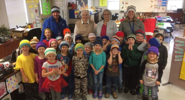 The local United Methodist Women's group recently knitted hats for Lincoln Elementary School kindergartners. Both Tom Cavalli and Jessica King's classed are pictured wearing their new hats when they were delivered earlier this month. Standing behind the students are (L-R) Tom Cavalli, United Methodist Women's representatives Jo Meili and Lana Houston, and Jessica King. (Courtesy Photo)