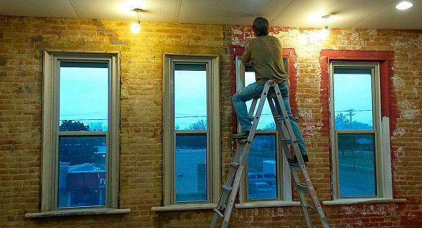 Craig Stertz works on the historic windows and brick wall as part of a building restoration on Lincoln Ave. in Lincoln, KS.