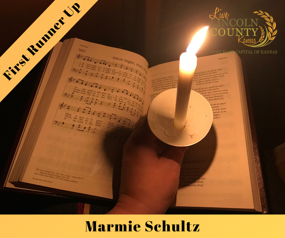 "First Runner-up winner of the 2019 #LiveLincolnCounty Photo Contest was Marmie Schultz, with a photo of a candle on a hymnal, titled ""Silent Night."""